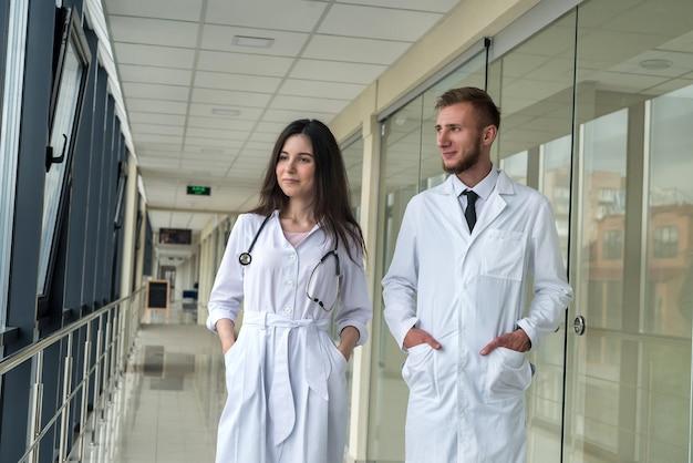 Schöne junge ärzte betrachten die kamera in der klinik. gesundheits- und medizinkonzept