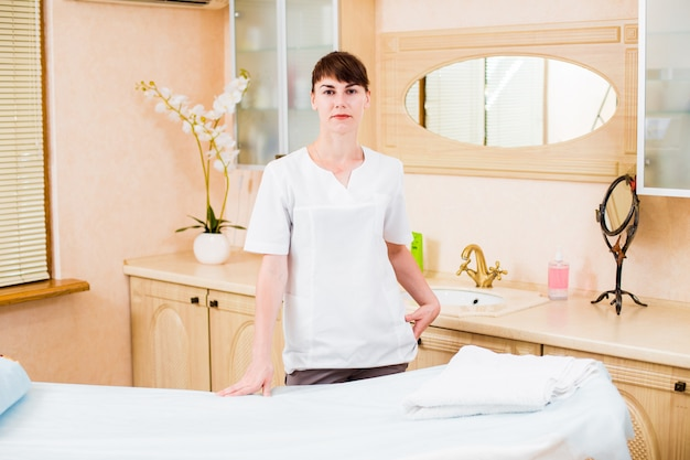 Schöne junge ärztin massagetherapeutin im büro, die nahe der couch aufwirft