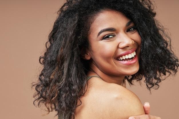 Schöne junge afrikanerin, die über die schulter lächelt und schaut