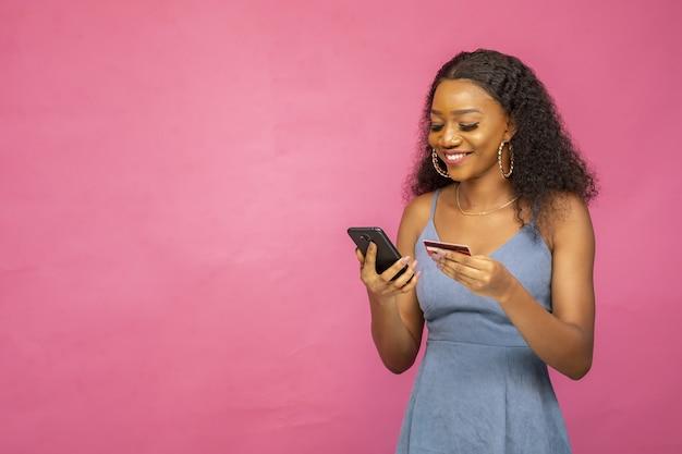 Schöne junge afrikanische frau, die ihr handy und ihre kreditkarte verwendet