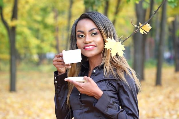 Schöne junge afrikanische frau, die kaffee von einer weißen tasse an der wand des herbstlaubs im park trinkt