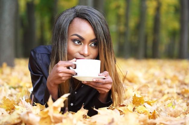 Schöne junge afrikanische frau, die kaffee von einer weißen tasse auf dem herbstlaub im park trinkt