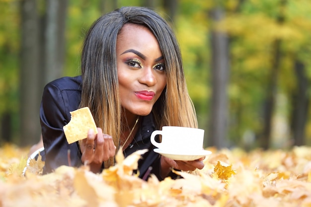 Schöne junge afrikanische frau, die kaffee von einer weißen tasse auf der oberfläche des herbstlaubs im park trinkt