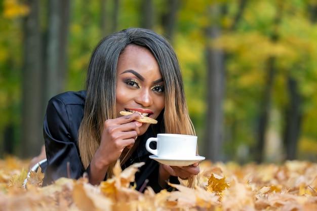 Schöne junge afrikanische frau, die kekse isst und kaffee im wald trinkt