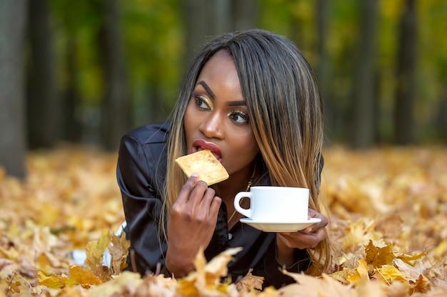 Schöne junge afrikanische frau, die kekse isst und kaffee vom weißen becher auf herbstlaub im park trinkt