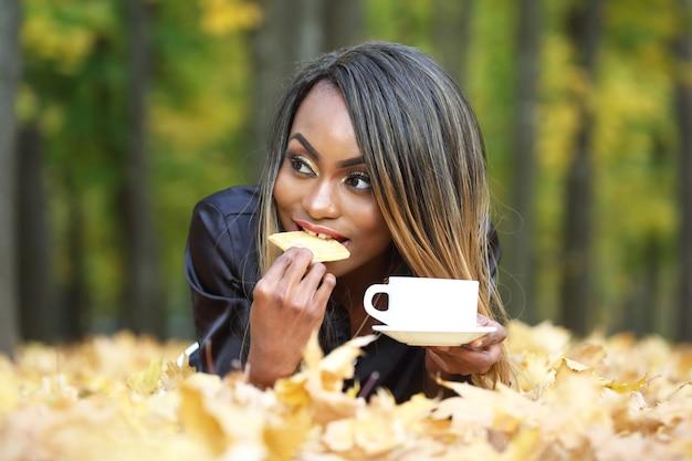 Schöne junge afrikanische frau, die kekse isst und kaffee von der weißen tasse auf herbstlauboberfläche im park trinkt