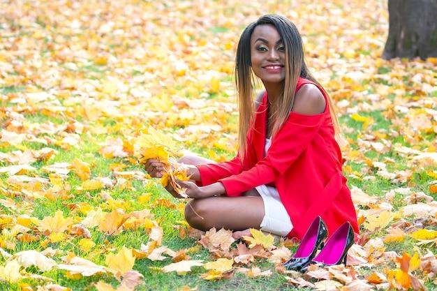 Schöne junge afrikanische frau herbstblätter