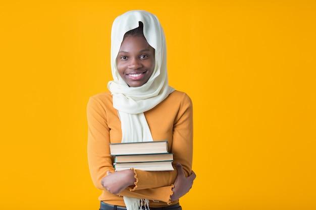 Schöne junge afrikanische frau mit einem muslimischen schal mit büchern in ihren händen