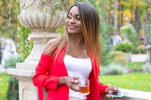 Schöne junge afrikanische frau mit einer tasse tee und einem telefon in ihren händen im park