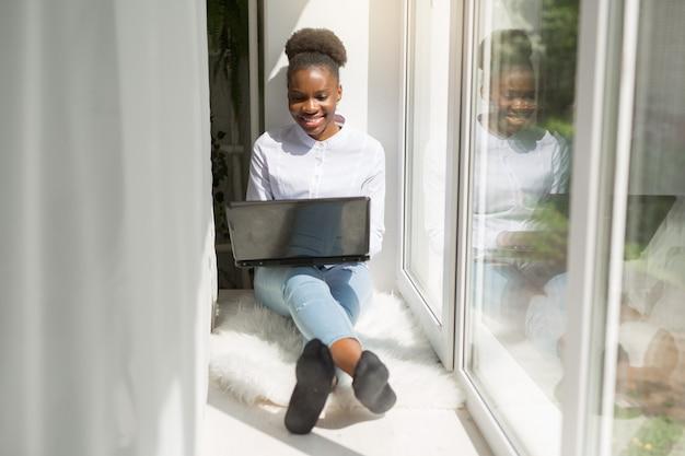 Schöne junge afrikanische frau mit laptop
