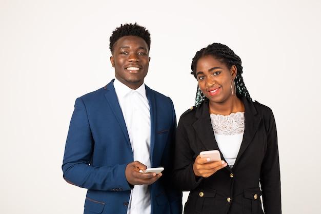 Schöne junge afrikanische leute auf einem weißen hintergrund mit telefonen in den händen