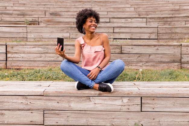 Schöne junge afro-amerikanerin, die handy verwendet, auf holztreppen sitzt und lächelt. holz hintergrund. lebensstil im freien