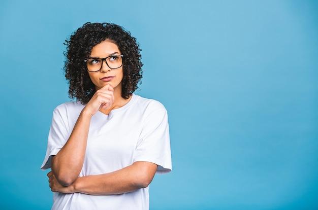 Schöne junge afroamerikaner-geschäftsfrau über lokalisiertem blauem hintergrund mit hand auf lippen, die über frage, nachdenklichen ausdruck nachdenken. mit nachdenklichem gesicht lächeln. zweifel konzept.