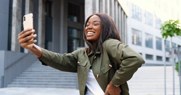 Schöne junge afroamerikanerfrau, die zur smartphone-kamera aufwirft und lächelt, während selfie-foto an der straße nimmt. ziemlich fröhliche stilvolle frau, die selfies bilder mit handy macht.