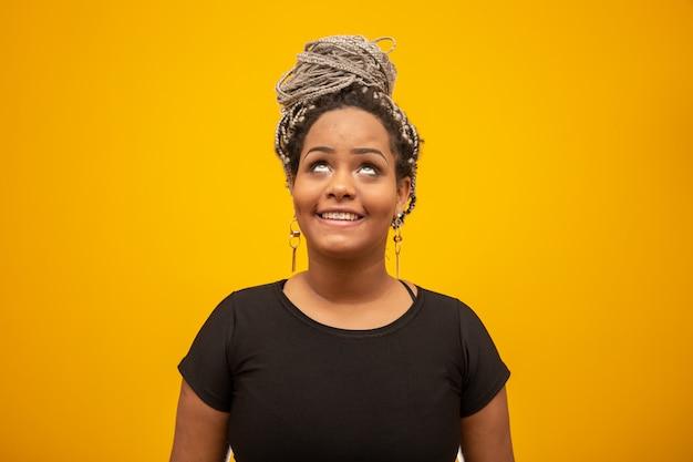 Schöne junge afroamerikanerfrau mit dem angsthaar auf gelb