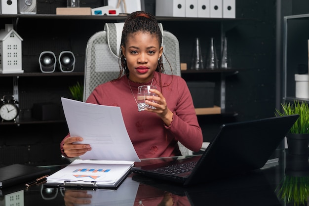 Schöne junge afroamerikanergeschäftsfrau, die glas wasser hält und bei tisch mit dokumenten im büro arbeitet