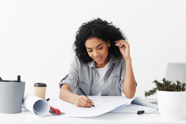 Schöne junge afroamerikanische frau architektin mit zeichnung des schwarzen lockigen haares mit stift