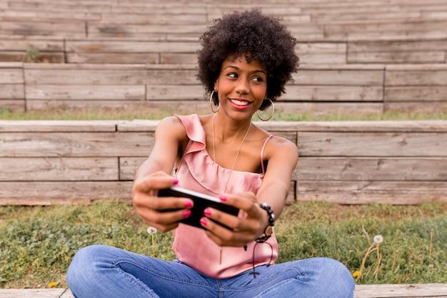 Schöne junge afroamerikanische frau, die ein foto mit handy macht, auf holztreppen sitzt und lächelt. holz hintergrund. lebensstil im freien