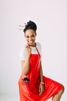 Schöne junge afroamerikanische kosmetikerin, die satz make-up-ausrüstung im sonderfall hält, lokalisiert auf weißem hintergrund