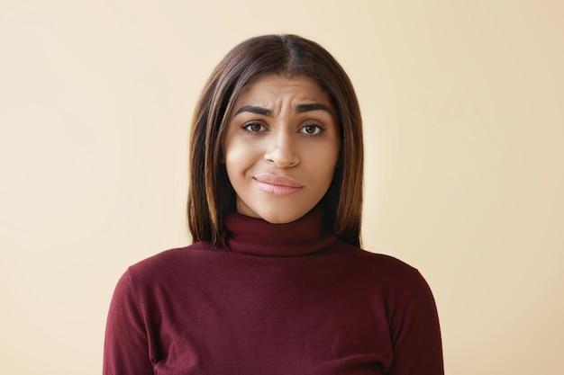 Schöne junge afroamerikanische mitarbeiterin mit dunklem glattem haar, die unzufrieden verärgert aussieht, sich frustriert und gestresst fühlt, während sie probleme und misserfolge bei der arbeit hat