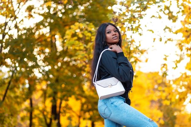 Schöne junge afroamerikanische modelfrau in modischer kleidung mit lässiger jacke mit stylischen blue jeans und einer modischen handtasche im park vor einem hintergrund von leuchtend gelbem herbstlaub