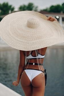 Schöne junge afrofrau im bikini, der den nahen swimmingpool trägt großen strohhut sich entspannt.