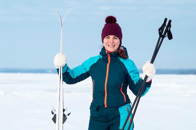 Schöne junge aktive frau, die draußen in einem winterschneetag steht und ski in händen hält