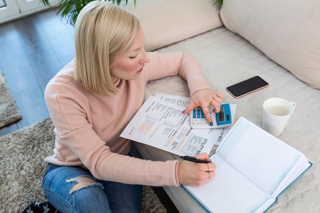 Schöne junge albino-frau, die mit taschenrechner und rechnungen sitzt und papierkram tut. handfrau, die finanzen tut und auf schreibtisch schreibt über kosten zu hause büro berechnet. konzeptarbeit von zu hause aus