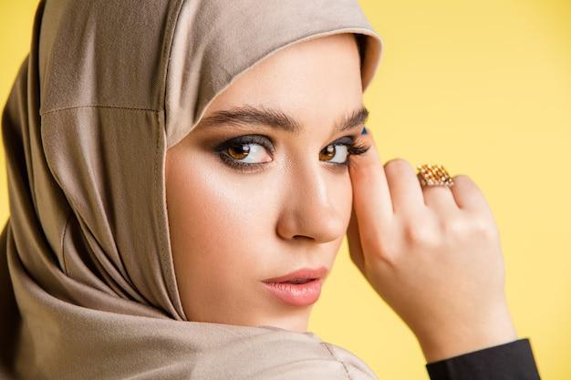 Schöne junge arabische frau im stilvollen hijab lokalisiert auf gelbem hintergrund mit copyspace