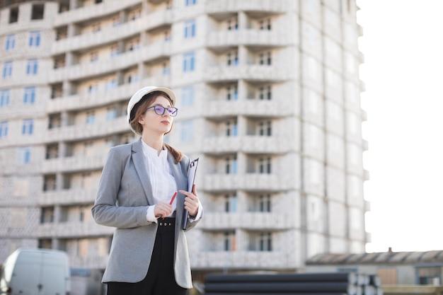 Schöne junge architektenfrau, die klemmbrett hält und weg schaut