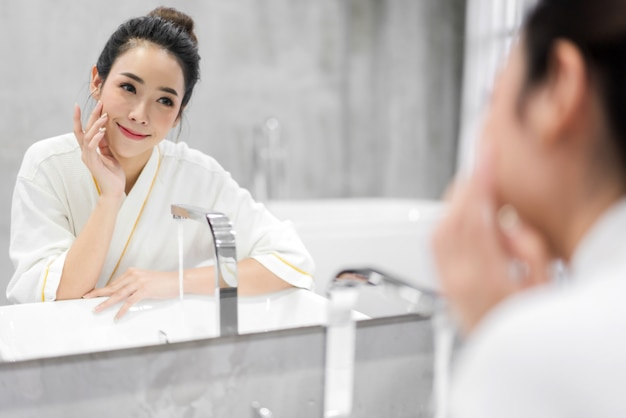 Schöne junge asiann frau, die sauberes gesicht mit wasser wäscht und vor dem spiegel im badezimmer lächelt. schönheit und spa. perfekte frische haut