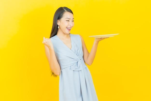 Schöne junge asiatin des porträts lächelt mit leerem teller