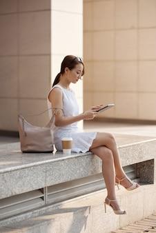 Schöne junge asiatin, die in der städtischen straße sitzt und tablette verwendet