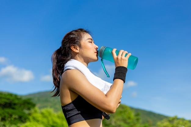 Schöne junge asiatin, die morgens an einer laufbahn, eine pause machend trainiert, um wasser zu trinken