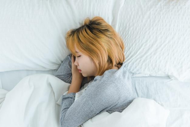 Schöne junge asiatin, die morgens im bett schläft