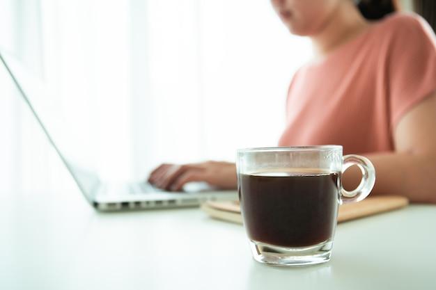 Schöne junge asiatin, die während der arbeit eine tasse heißen schwarzen kaffee auf dem tisch hält. asiatische junge frau trinkt morgens gerne einen heißen kaffee, bevor sie von zu hause aus mit dem online-meeting beginnt.