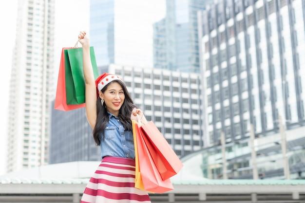 Schöne junge asiatin in buntem kleid, die die einkaufstasche hochhält, die sie mit einem glücklichen lächeln gekauft hat, weil sie sie ihren freunden, freunden und familienmitgliedern zu weihnachten schenken wird