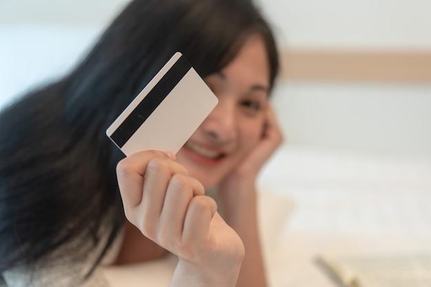 Schöne junge asiatin zeigen ihre kreditkarte für online einkaufen