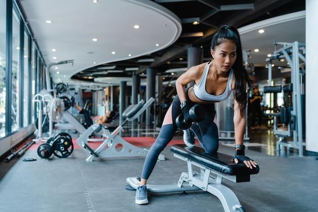 Schöne junge asiatische dame, die das fettverbrennungs-training der langhantel in der fitnessklasse macht.