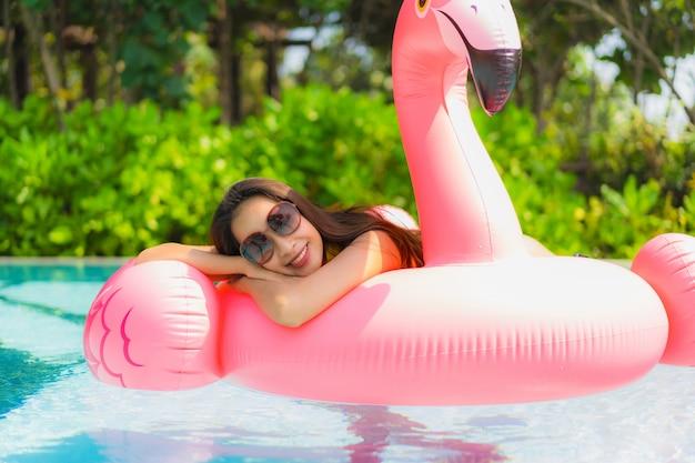 Schöne junge asiatische frau des porträts auf dem aufblasbaren flamingofloss im swimmingpool am hotelerholungsort