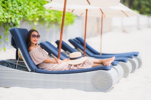 Schöne junge asiatische frau des porträts auf dem klappstuhl mit regenschirm um strandseeozean