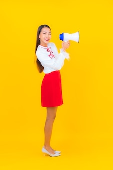 Schöne junge asiatische frau des porträts benutzen megaphon auf gelb