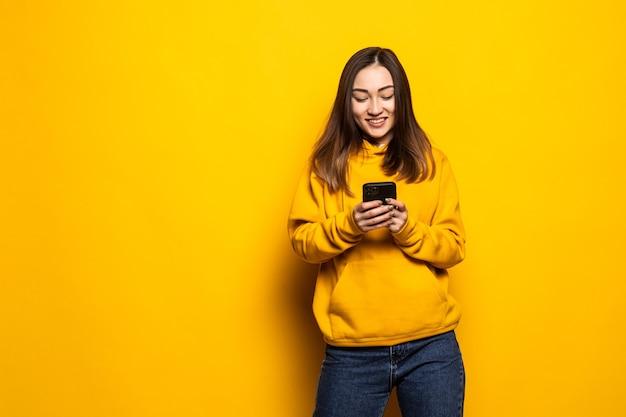 Schöne junge asiatische frau des porträts benutzt intelligentes handy auf gelber wand