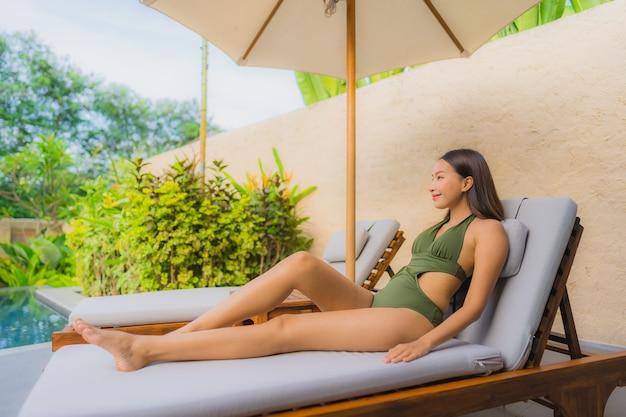 Schöne junge asiatische frau des porträts, die auf der stuhlplattform mit nahem swimmingpool des regenschirmes sitzt