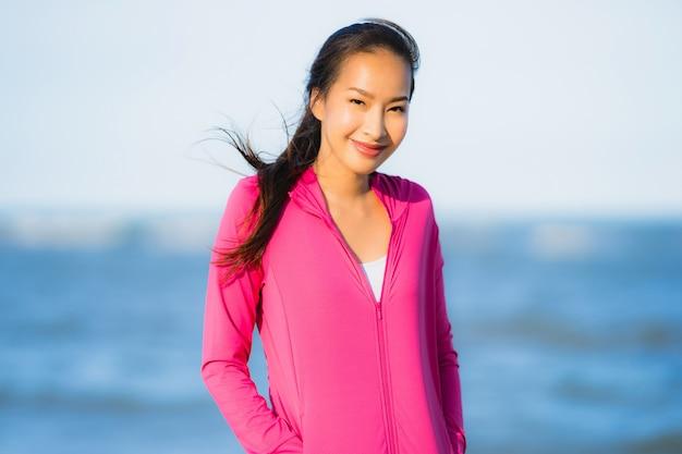 Schöne junge asiatische frau des porträts, die auf der tropica naturlandschaft des strandes läuft oder trainiert