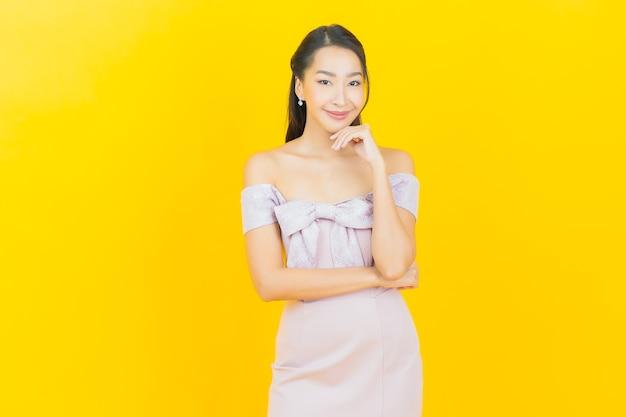Schöne junge asiatische frau des porträts, die auf farbwand lächelt und aufwirft