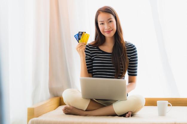 Schöne junge asiatische frau des porträts, die computernotizbuch oder laptop mit kreditkarte für den einkauf verwendet