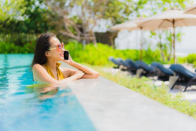 Schöne junge asiatische frau des porträts, die handy oder mobiltelefon im swimmingpool verwendet