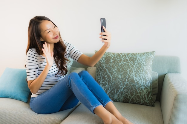 Schöne junge asiatische frau des porträts, die handy verwendet oder spricht