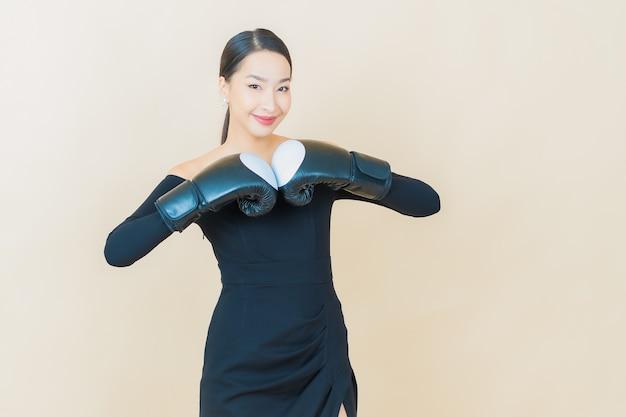 Schöne junge asiatische frau des porträts, die mit handschuh auf gelb boxt